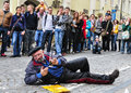 Unusual expressions on the street of a man lying down with a glass of beer in streets of vilnius lithuania Royalty Free Stock Photography