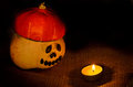 Unusual helloween orange hat pumpkin andcandle fire cheerful halloween and candle on sackcloth jute background Stock Image