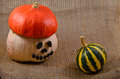 Unusual helloween orange hat pumpkin and small watermelon halloween autumn harvest on sackcloth jute background Stock Images
