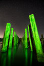 Unusual poles in the water at night on a background stars green reflection with deep sky Stock Photography