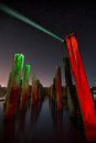 Unusual poles in the water at night on a background stars red reflection with deep sky Stock Photography