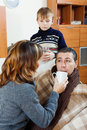 Unwell man surrounded by caring wife and son men at home Royalty Free Stock Image