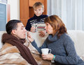 Unwell man surrounded by caring wife and son men in living room Stock Images