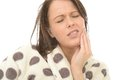 Unwell sick poorly young woman with a painful toothache in her twenties holding her face her hand facial Royalty Free Stock Images