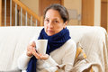 Unwell woman in blue scarf sitting at home Stock Images