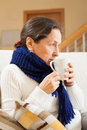 Unwell woman in scarf ailing middle aged sitting on couch with cup of tea Royalty Free Stock Photos