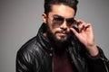 Uomo con la riparazione lunga della barba o mettere sui suoi occhiali da sole Fotografie Stock Libere da Diritti