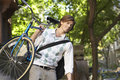 Uomo d affari carrying bicycle outdoors Fotografie Stock Libere da Diritti