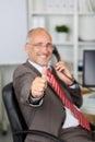 Uomo d affari gesturing thumbs up mentre per mezzo del telefono della linea terrestre Fotografia Stock