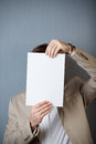 Uomo d affari holding blank paper in front of face Immagine Stock