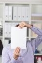 Uomo d affari holding blank paper in front of face in office Fotografia Stock Libera da Diritti