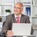 Uomo d affari with laptop looking via in ufficio Fotografie Stock Libere da Diritti