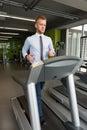 Uomo d affari running on treadmill in palestra Immagini Stock Libere da Diritti