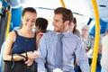 Uomo d affari and woman looking al telefono cellulare sul bus Fotografia Stock Libera da Diritti