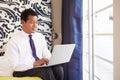 Uomo d affari working on laptop nella camera di albergo Immagine Stock Libera da Diritti