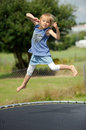 Up in the air a girl jumping on a trampoline Royalty Free Stock Photos