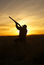 An upland game hunter with shotgun up silhouetted against a sunset Royalty Free Stock Photos