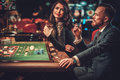 Upper class couple gambling in a casino Royalty Free Stock Photo