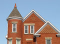 Upper story red brick house steep roofs round corner tower isolated against blue sky Royalty Free Stock Photos