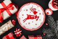 Upper top view of a red ribbon, Christmas presents, tree toys, deer plate and evergreen branch on a stone black background. Royalty Free Stock Photo