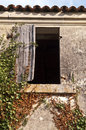 Upper window of derelict farm house and shutter french with ivy climbing up stone wall grey weather beaten shutter Royalty Free Stock Photo