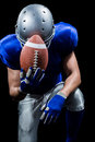 Upset american football player kneeling while holding ball against black background Stock Photography