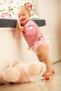 Upset Baby Girl Learning To Stand Up At Home Royalty Free Stock Photography