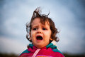 Upset baby yelling with windblown hair Royalty Free Stock Photography