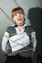 Upset businesswoman bound by contract terms scared and conditions afraid and helpless woman tied to chair become slave human hand Royalty Free Stock Image