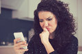 Upset confused young woman looking at mobile phone reading text message Royalty Free Stock Photo