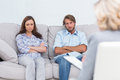 Upset couple sit on a sofa with arms crossed during psychotherapy Stock Photography