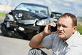 Upset driver man after car crash adult discussing on mobile phone in front of automobile collision accident in city road Royalty Free Stock Image