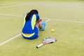 Upset female tennis player is sitting on the court Royalty Free Stock Photo