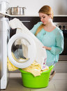 Upset girl with dirty linen after laundry