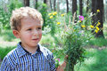 Upset little boy with a bouquet of flowers in the summer in the woods is frustrated Stock Photo