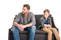 Upset little boy with crossed arms and father sitting on sofa and looking away Royalty Free Stock Photo