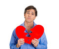 Upset man with broken heart closeup portrait young sad confused holding in his hands about to cry isolated white background Royalty Free Stock Photo