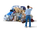 Upset man w laundry basket huge pile of clothes a distraught with his hand to his head and a in his hand is standing in front a Royalty Free Stock Photography