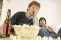Upset men watching tv with popcorn and beer on table young bottle Stock Image