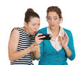 Upset on mobile cell phone closeup portrait of two women looking shocked while watching something their text message ams email Stock Photography