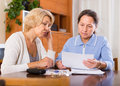Upset pensioners with documents sad female reading faces at home focus on blonde Stock Photos
