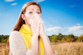 Upset tissue sneezing female outdoors with blue sky Stock Image