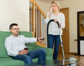 Upset woman cleaning around man resting with beverage his sad wife focus on man Stock Images