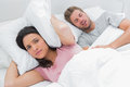 Upset woman covering ears with pillow next to husband snoring while her is her Royalty Free Stock Photography