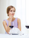 Upset woman with glass of whine waiting for date reastaurant and happiness concept young red at restaurant Stock Photography