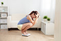 Upset woman on weigh scale Royalty Free Stock Photo