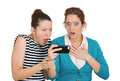 Upset women on mobile cell phone closeup portrait of two looking shocked while watching something their text message ams email Stock Image