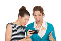 Upset women on mobile cell phone closeup portrait of two looking shocked while watching something their text message ams email Stock Images