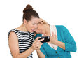Upset women on mobile cell phone closeup portrait of two looking shocked while watching something their text message ams email Stock Photos