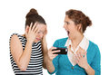 Upset women on mobile cell phone closeup portrait of two looking shocked while watching something their text message ams email Royalty Free Stock Photo